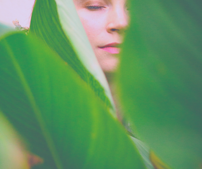 Mysterious woman hidden behind leaves